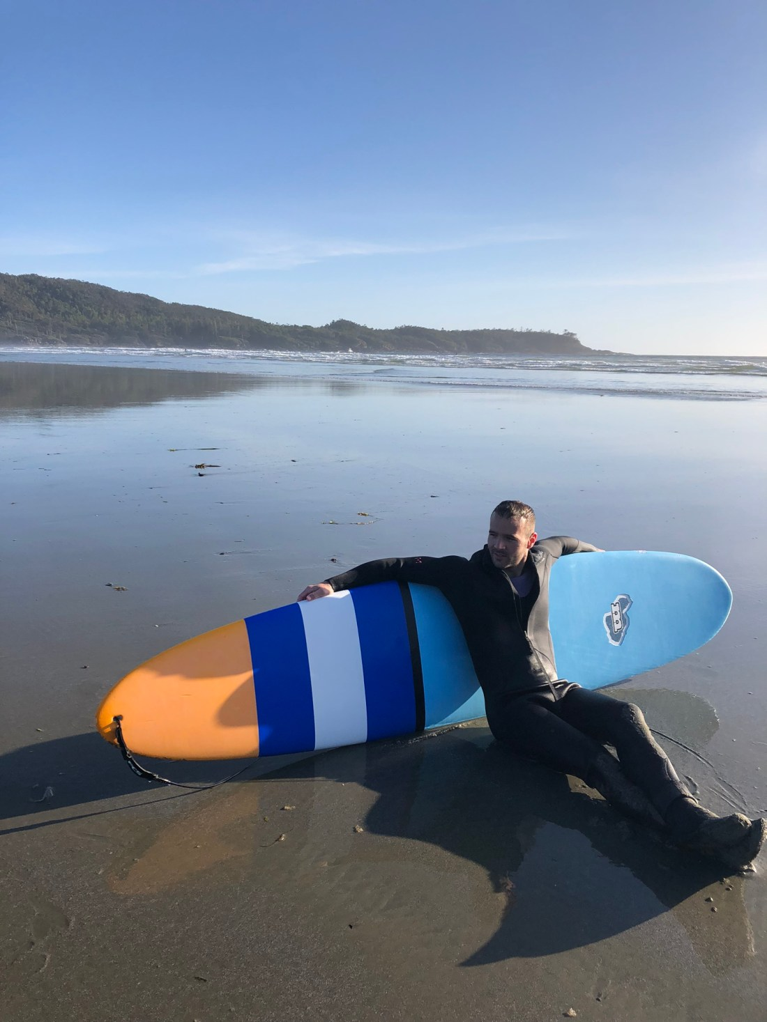 Relaxing with the surfboard on Cox Bay Beach