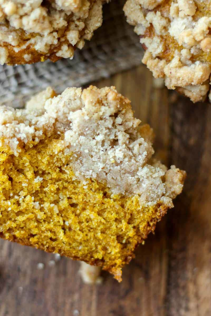 pumpkin muffin cut in half on the table so you can see the pumpkin muffin and streusel layers