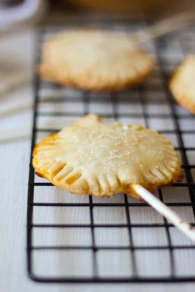 Pumpkin Pie Pops are the perfect thanksgiving dessert recipe! Use premade pie crust to cut out pumpkin shaped dough and fill with pumpkin pie filling. Bake with a stick and you have the perfect mini bite-size dessert for fall that everyone will love. The best part is they're individual so everyone can have one and eat whenever they want.