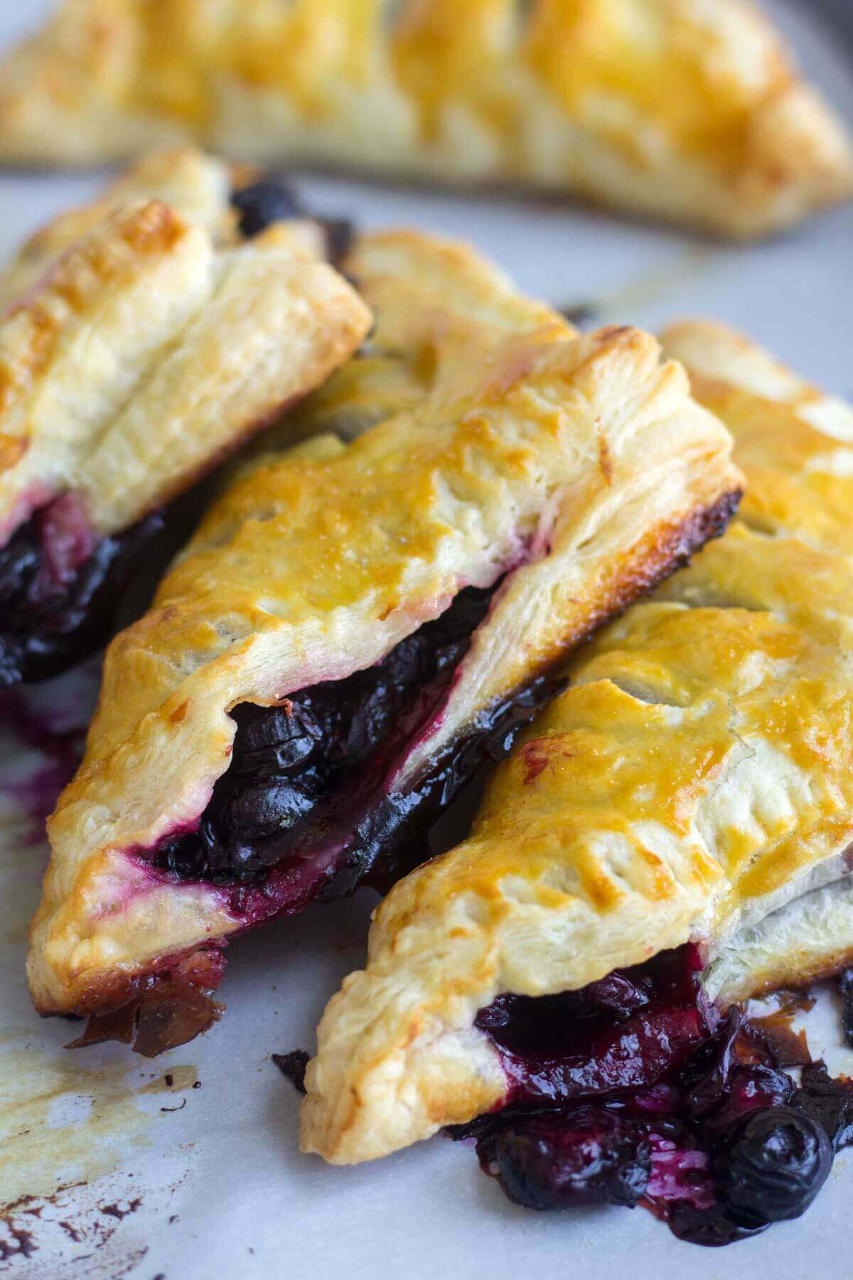 3 lemon blueberry turnovers baked golden brown on a baking pan with parchment paper