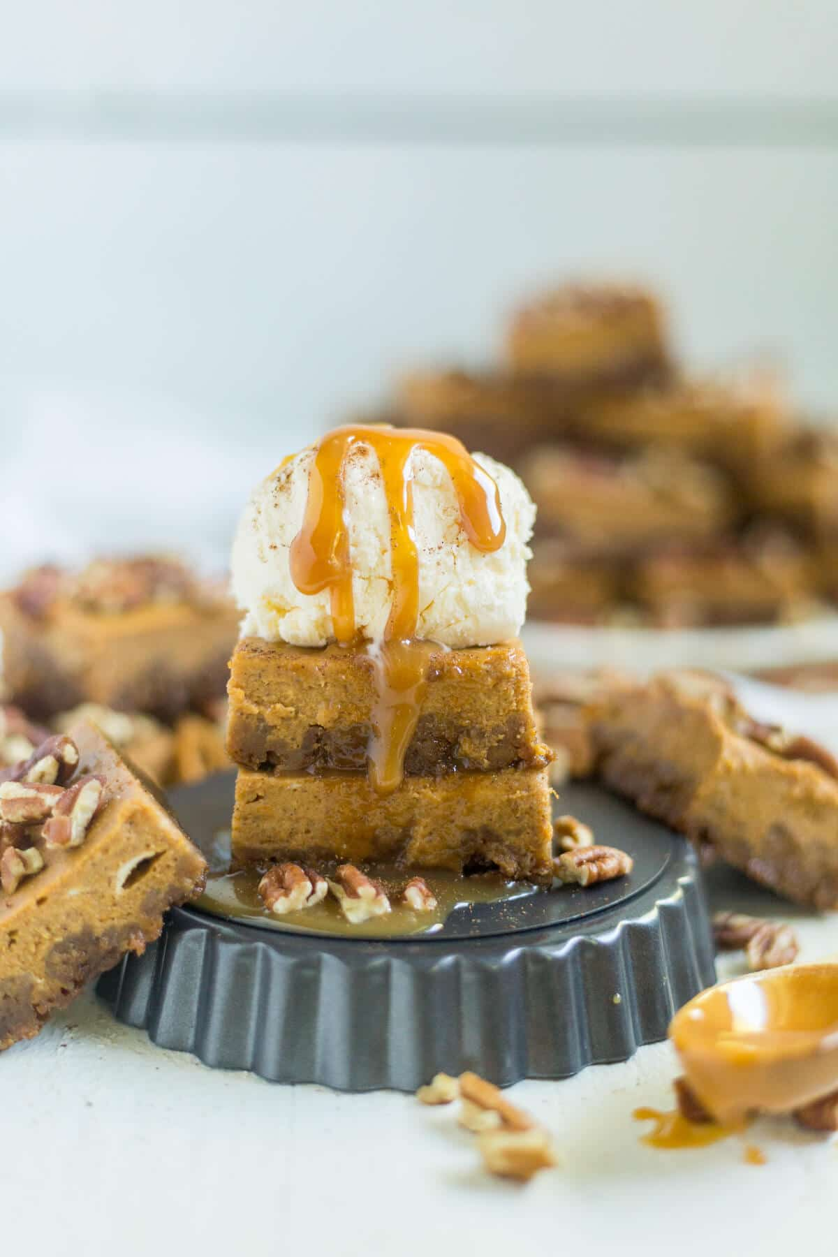 Pumpkin pie bars are a fun twist on a classic Thanksgiving recipe! The crust is made from crushed gingerbread and the bars are just like pumpkin pie and topped with pecans, caramel, ice cream and more!