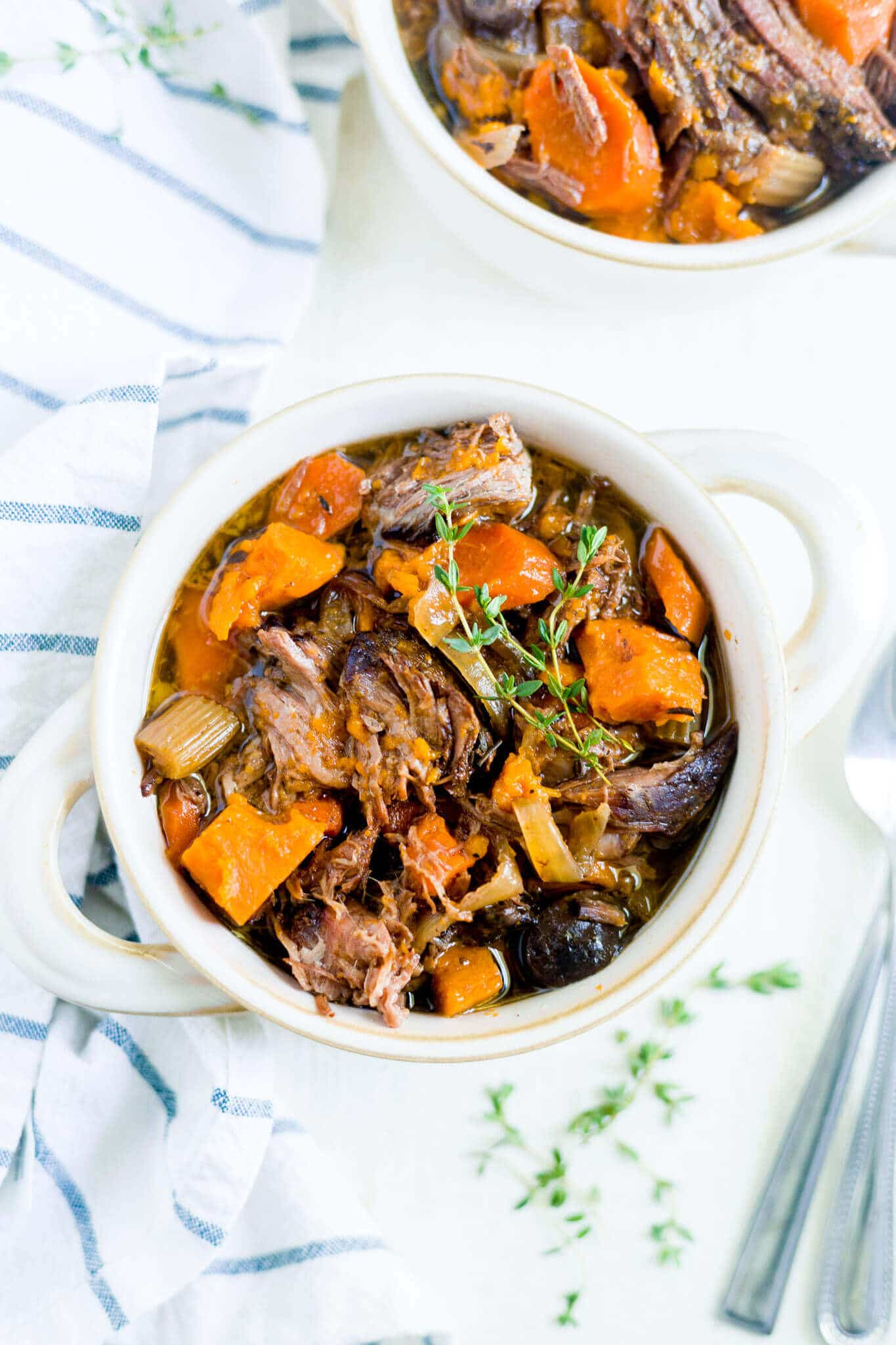 sweet potato beef stew in a bowl with fresh thyme