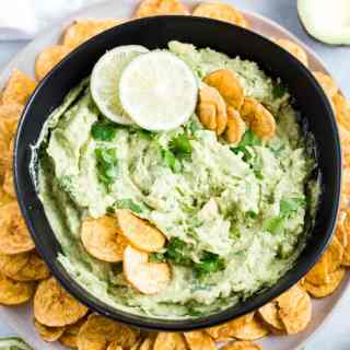 avocado dip in a black bowl with lime, cilantro and plantain chips
