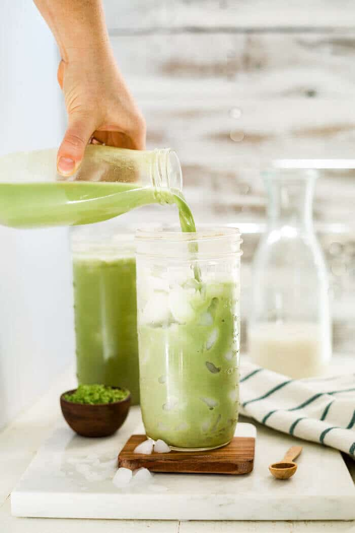 iced matcha latte being poured into a tall glass