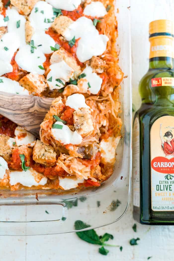olive oil bottle sitting next to spaghetti squash casserole