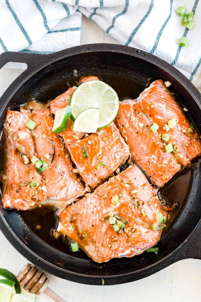 4 wild caught salmon filets with honey glaze in a skillet with lime and green onion