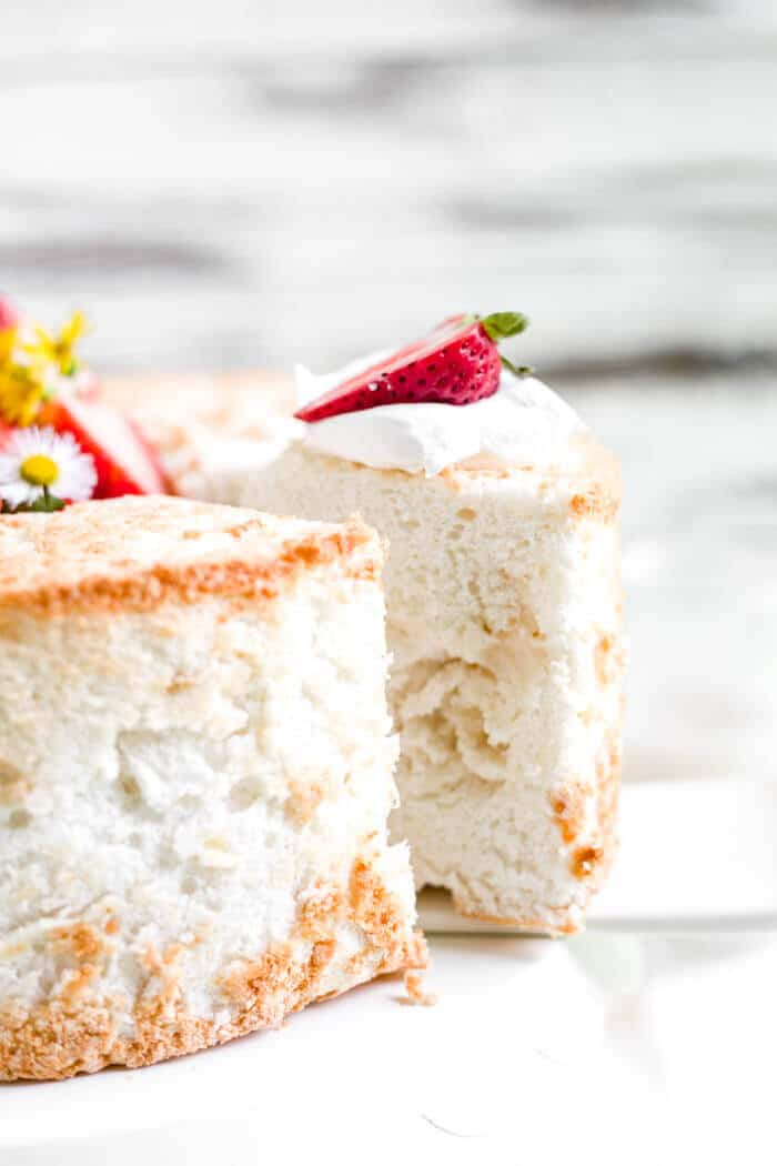 a slice of gluten free angel food cake being removed from the cake