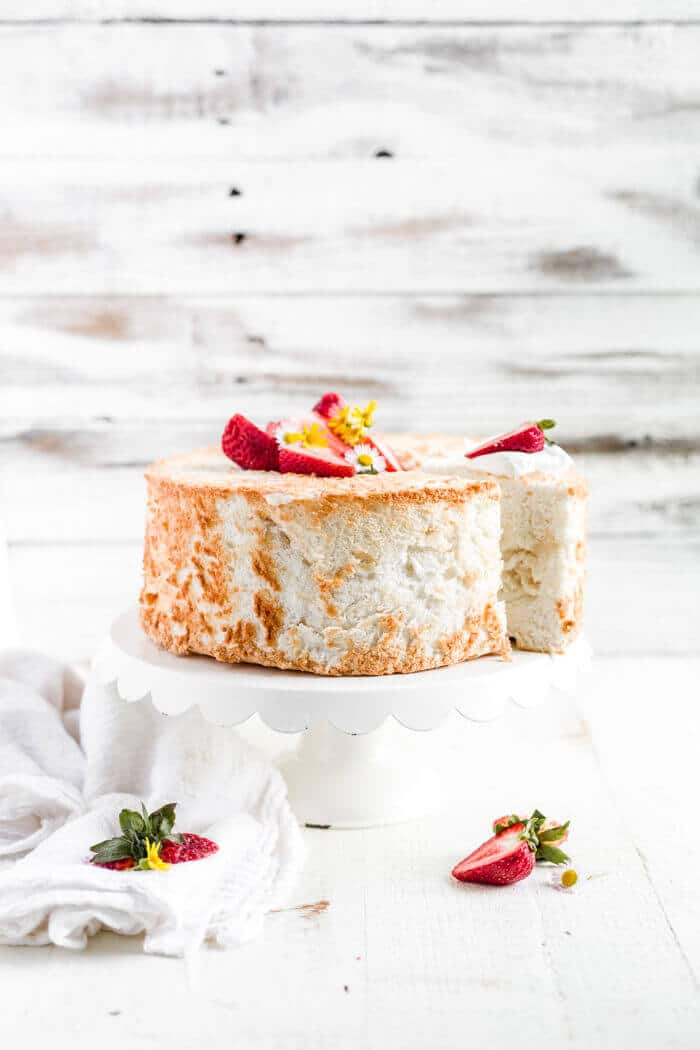 gluten free angel food cake on a cake stand with strawberries