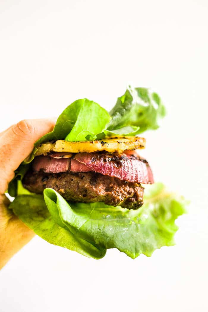 hand holding a teriyaki burger on the grill in a lettuce wrap