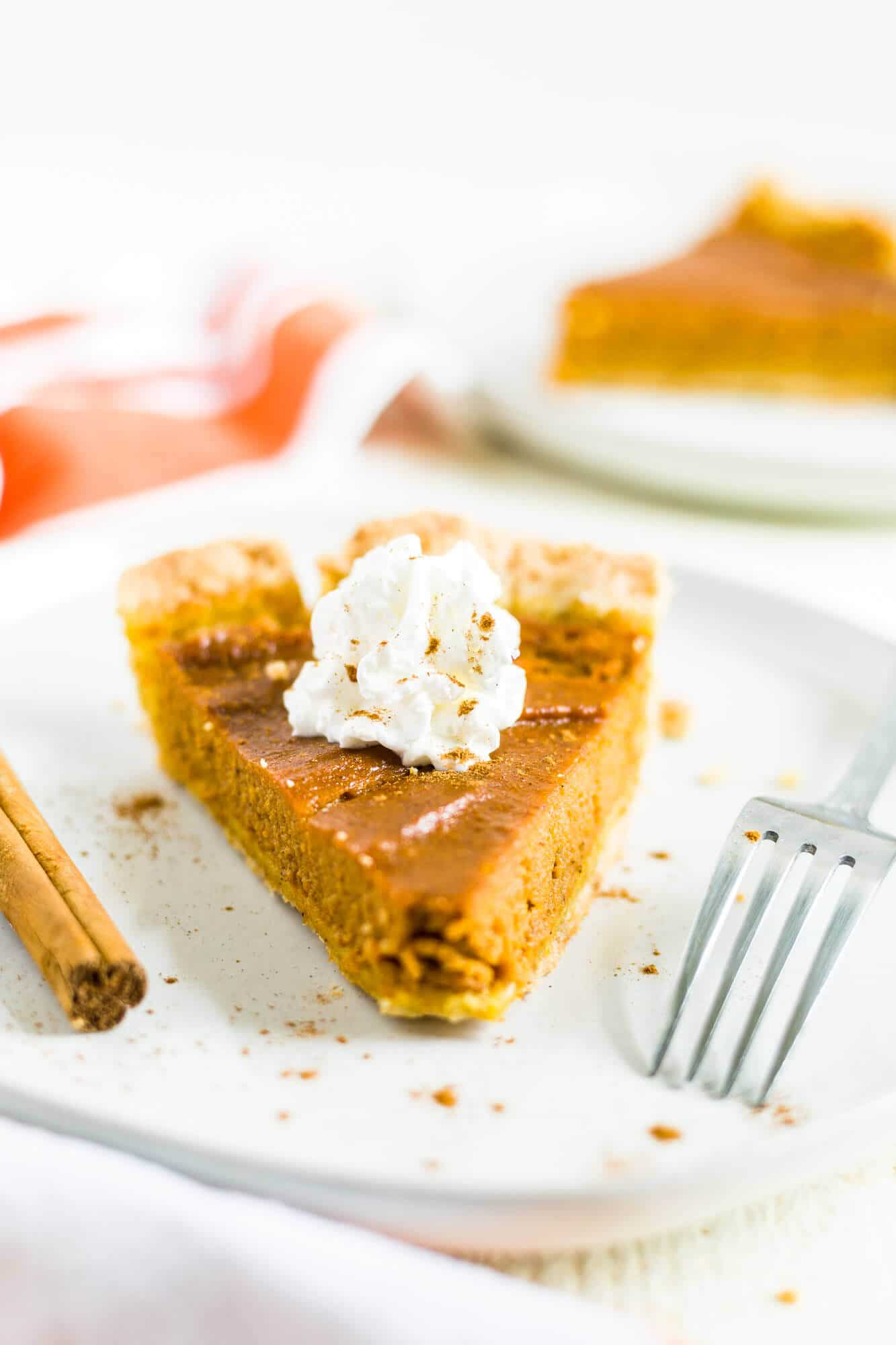 gluten and dairy free pumpkin pie sliced perfectly sitting on a white plate with a dollop of whipped cream and cinnamon
