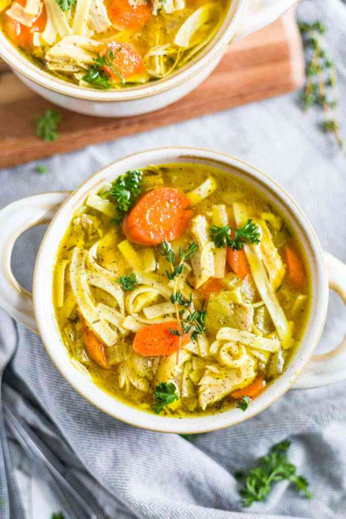 the best instant pot chicken noodle soup with carrots, shredded chicken and topped with fresh parsley