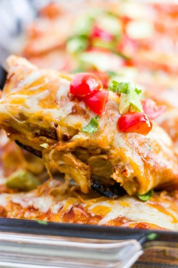 spatula scooping out a healthy chicken enchilada with stringy cheese topped with tomato and avocado