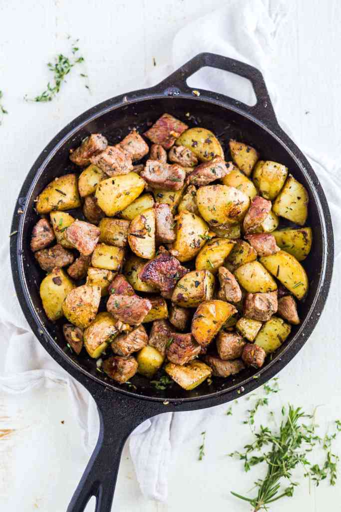steak bites and potatoes in a cast iron skillet