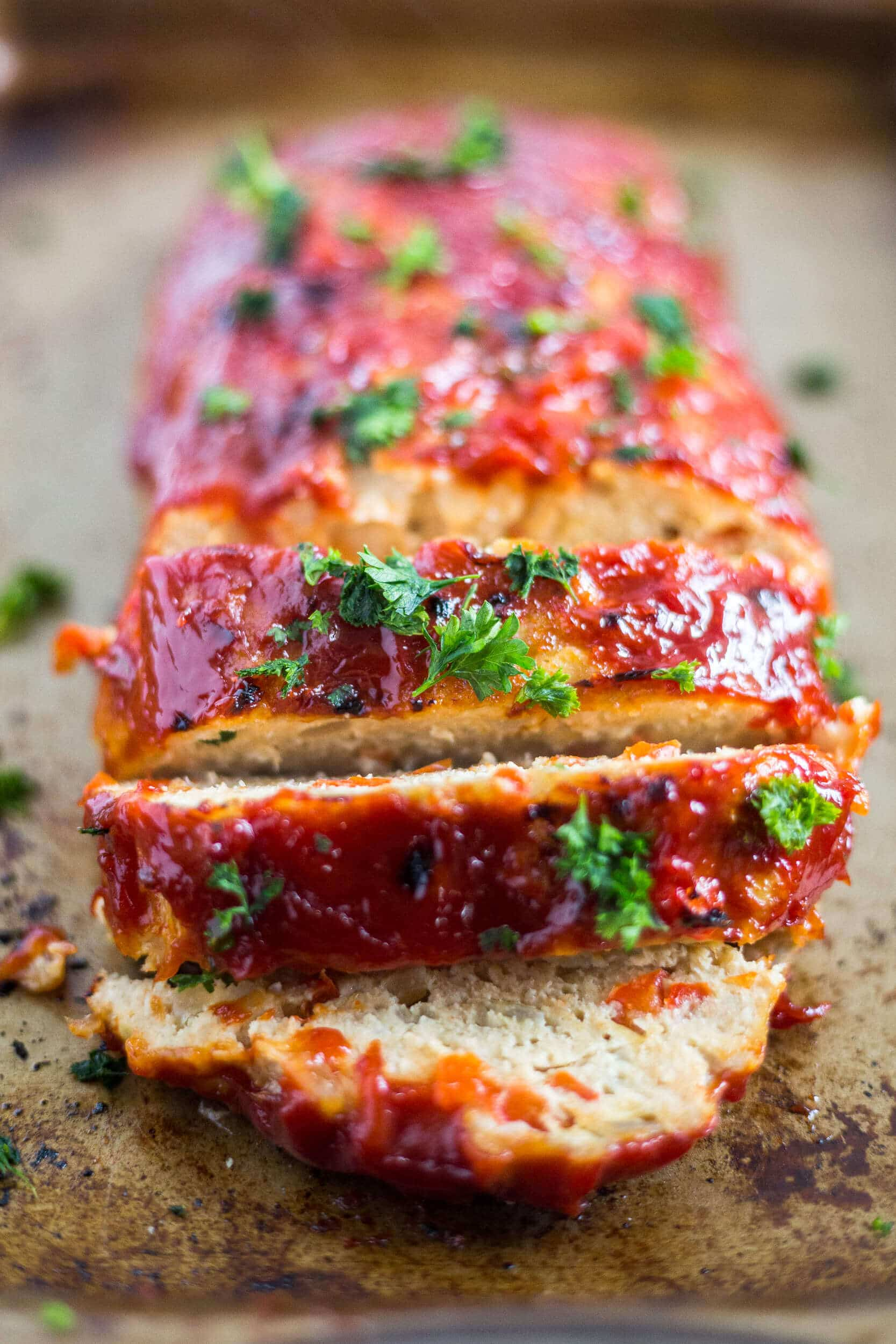 gluten free turkey meatloaf with a ketchup glaze sliced on a baking sheet