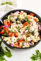 Italian pasta salad in a black bowl with fresh herbs