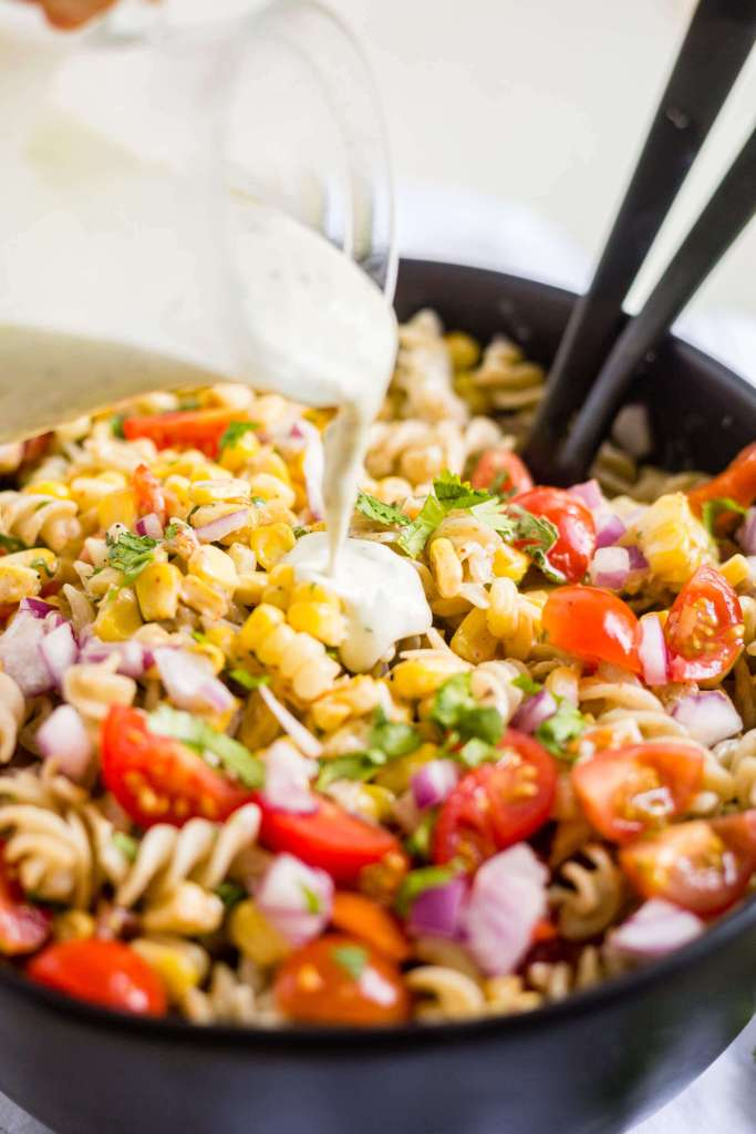 dairy free creamy jalapeno dressing being poure on mexican pasta salad