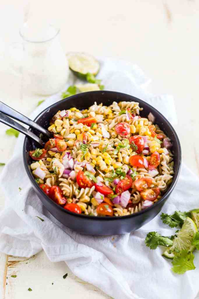 Mexican pasta salad in a black bowl with serving spoons