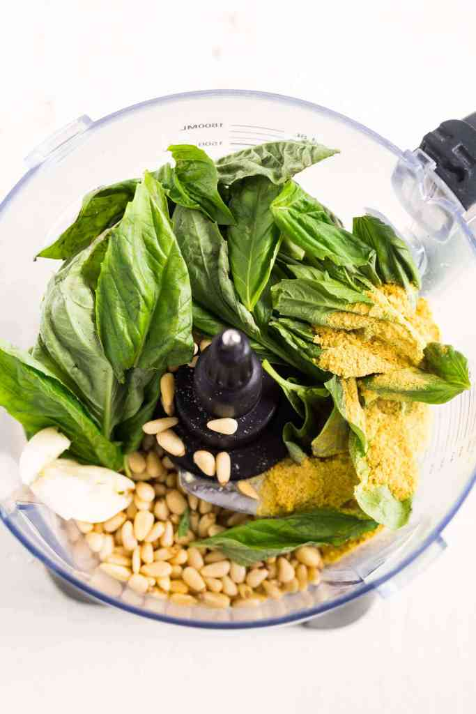 ingredients for vegan pesto in the bowl of a food processor