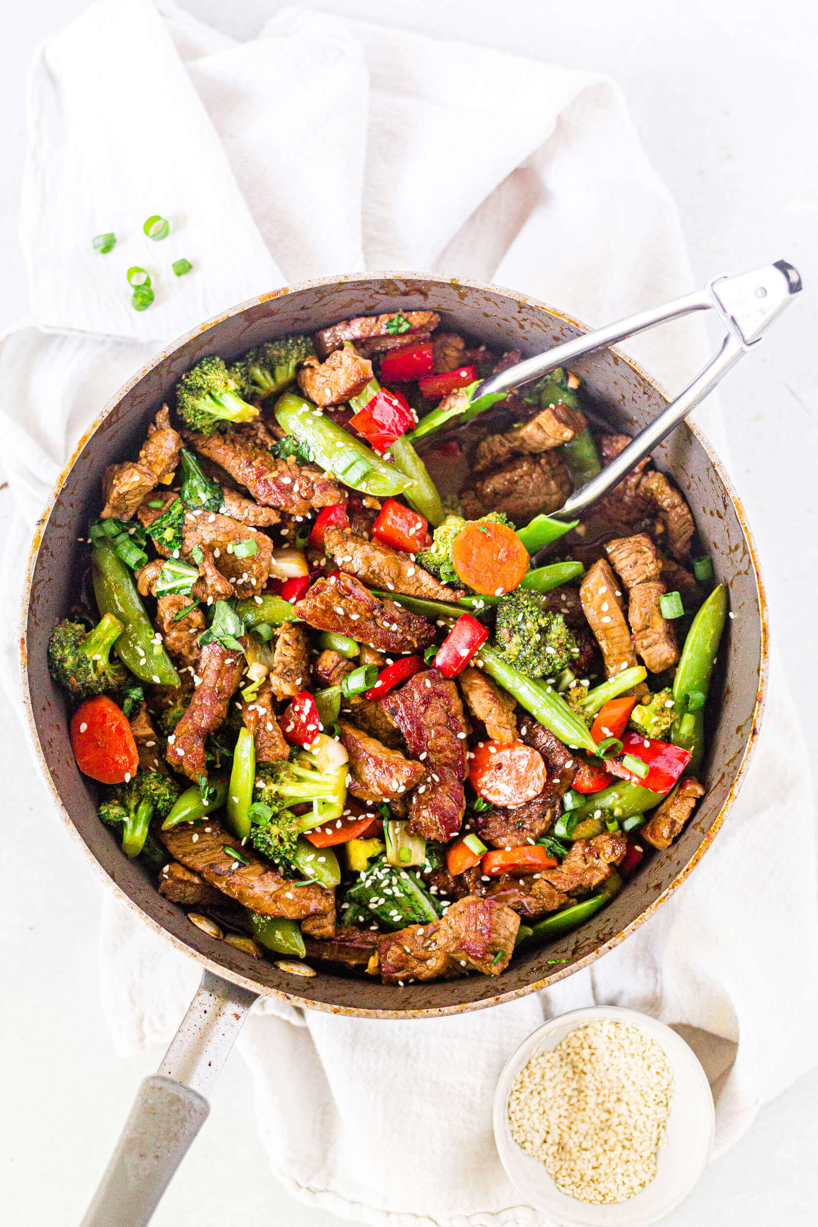 veggie packed steak stir fry in a frying pan with tongs and sesame seeds