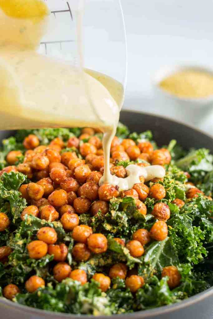 kale salt with roasted chickpeas in a grey bowl with vegan caesar dressing being poured on top