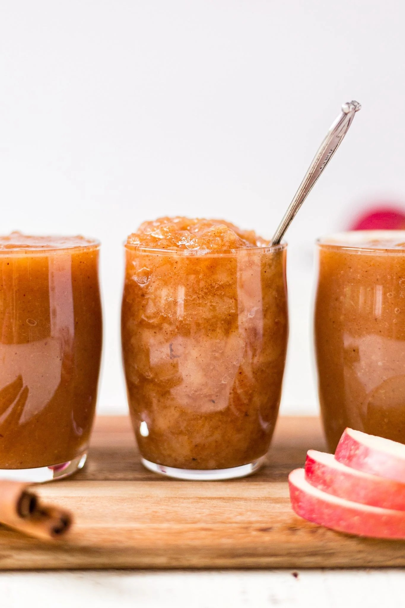 crockpot applesuace recipe in a cup with a spoon