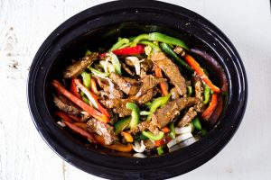 pepper steak ingredients in a crock pot before cooking