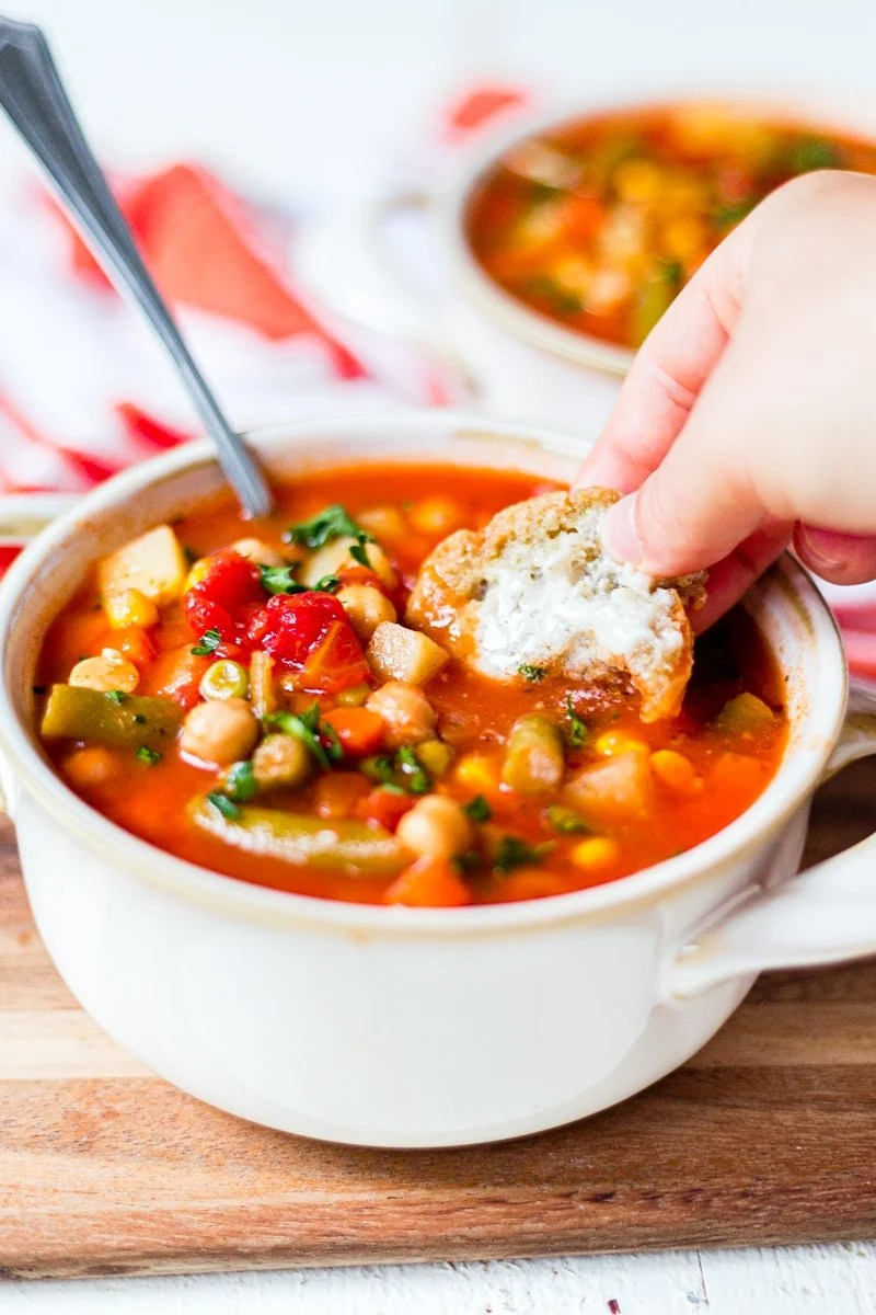 dipping buttered bread into a bowl of hot vegetable soup