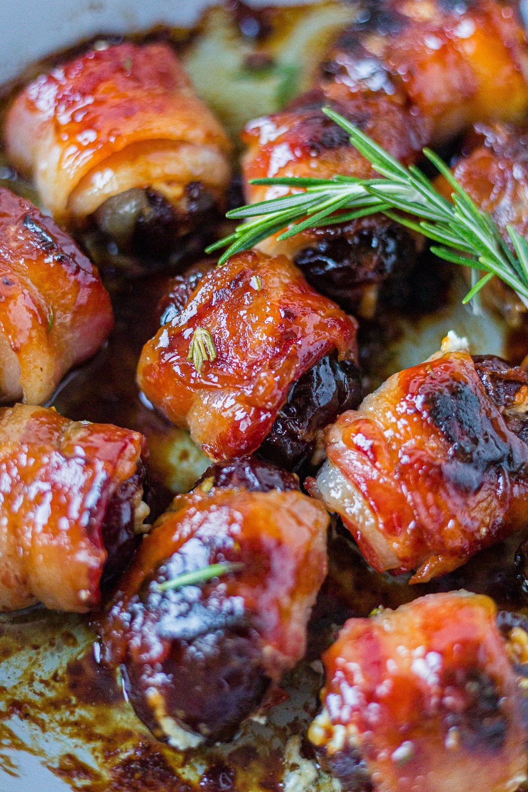 bacon wrapped dates cooked crispy on a pan with a sprig of fresh rosemary