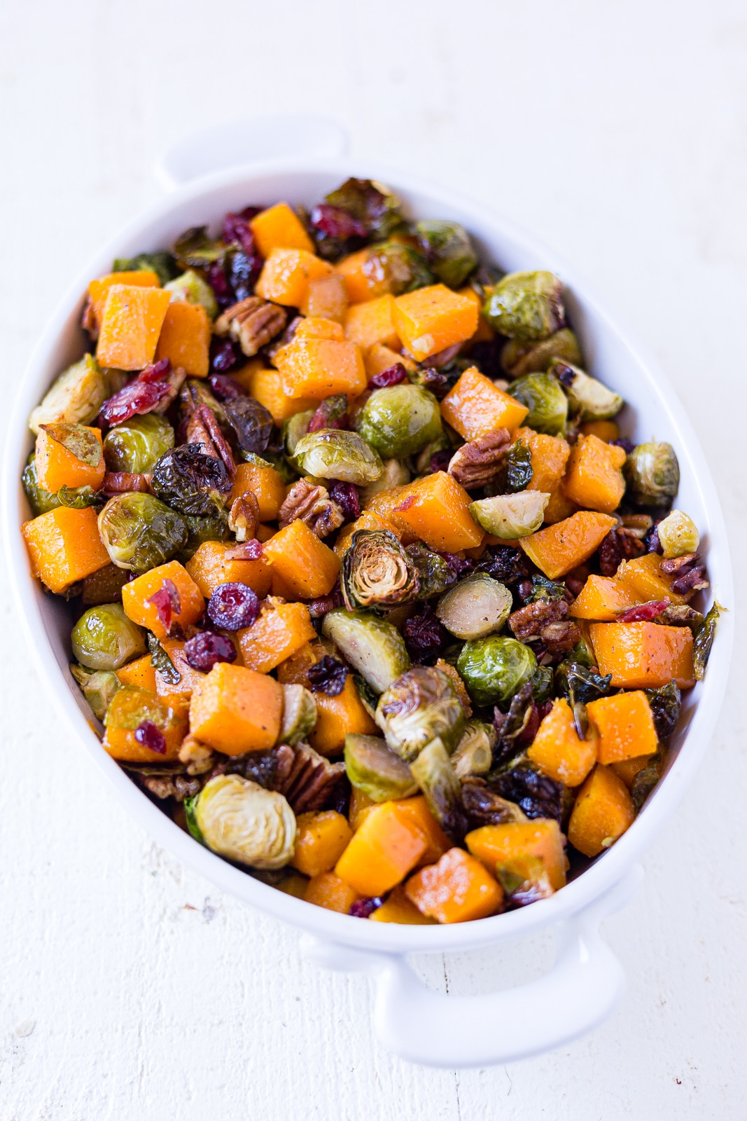 butternut squash and brussel sprouts in a serving bowl with cranberries and pecans