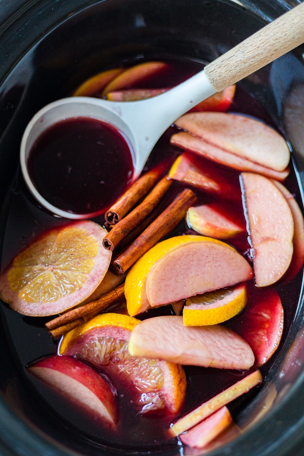 winter sangria recipe in a crock pot with sliced apples, oranges and cinnamon sticks