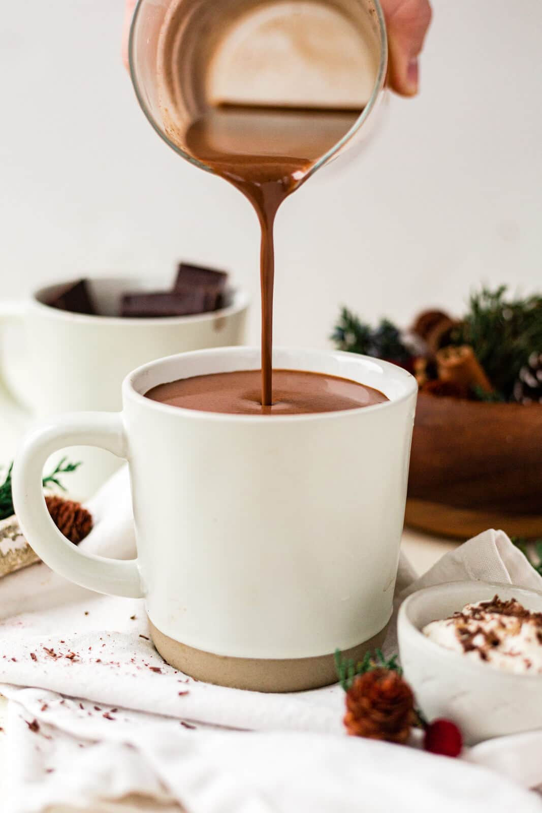 pouring thick and creamy healthy hot chocolate into a white mug with christmas greenery around it