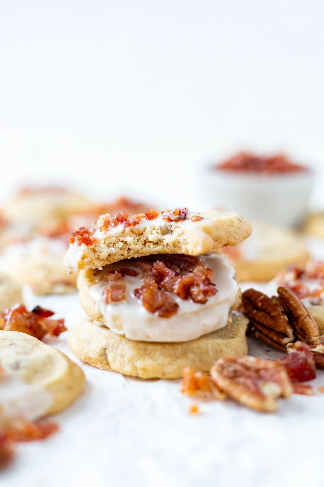 a stack of pecan shortbread cookies with a bite taken out of the top cookie