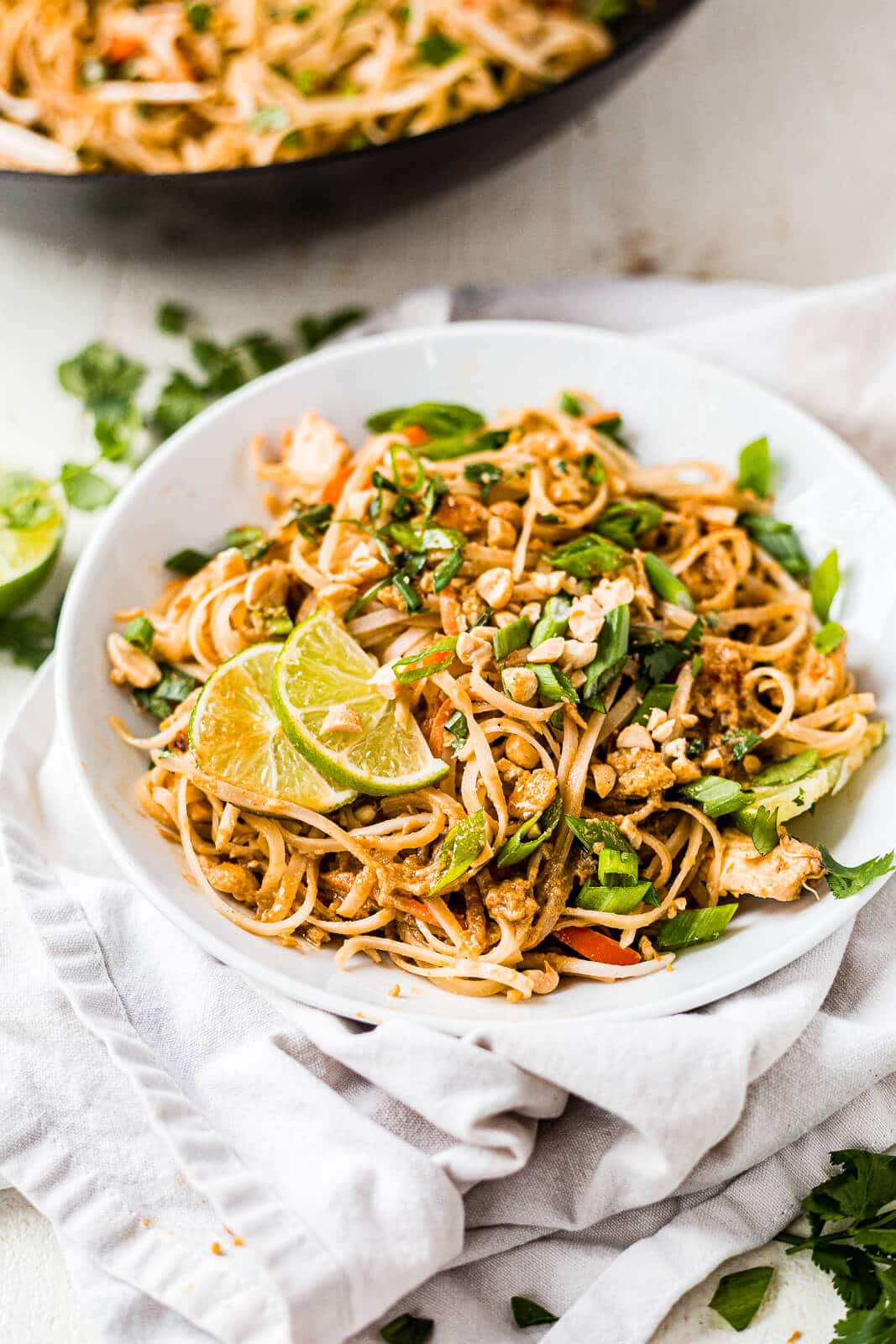 chicken pad thai topped with green onion, cilantro and lime in a shallow white bowl with a white napkin