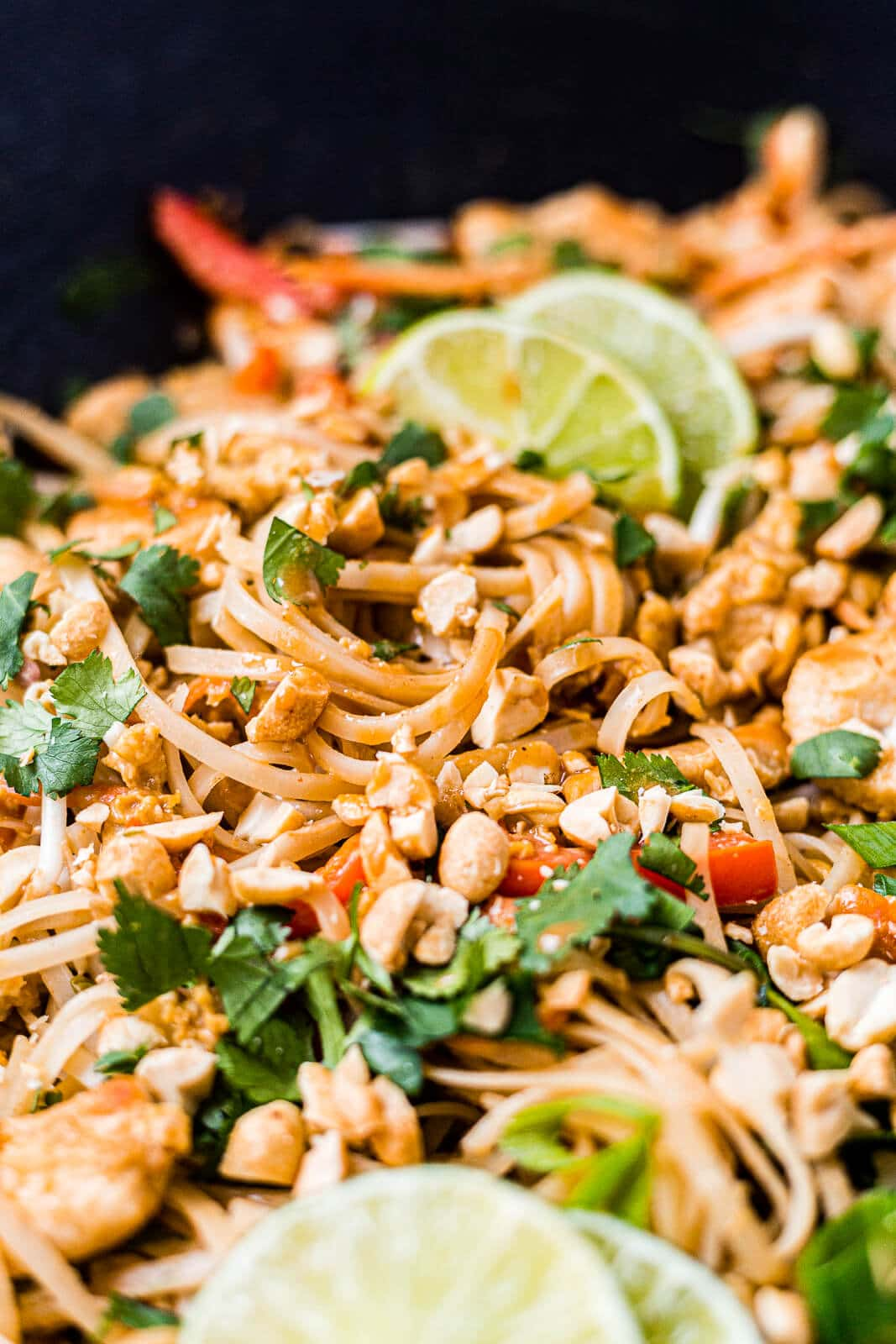 close up picture of chicken pad thai in a wok topped with cilantro, green onion and peanuts with lime wedges