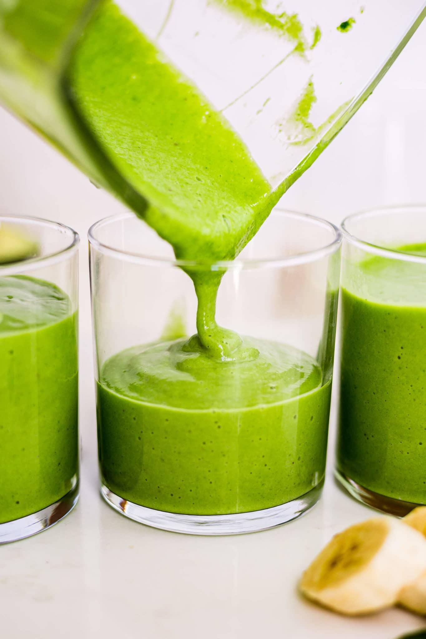 green avocado smoothie pouring into a short glass form the blender