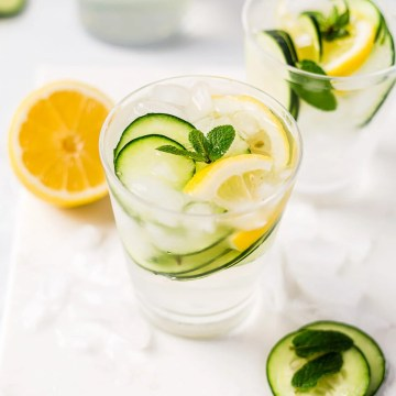 fresh cucumber water in a glass cup with lemon and a sprig of mint