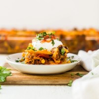 layers of mexican lasagna on a white plate topped with sour cream, salsa and cilantro