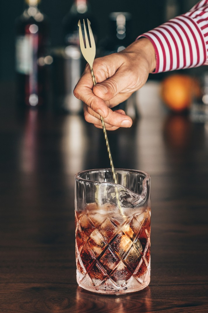 Negroni---stirring-in-stirring-glass-with-gold-bar-spoon
