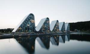 Ten pofalowany budynek wpasowuje się w krajobraz duńskich fiordów