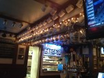 Mugs are suspended above the bar and seating areas that belong to Ugly Mug Club members.
