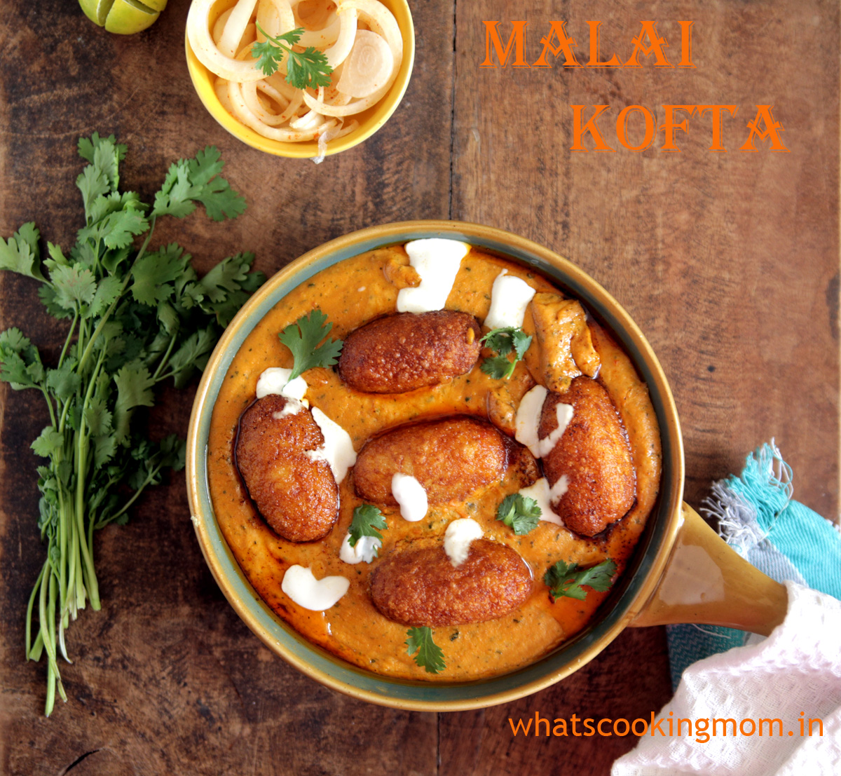 Malai Kofta served in a ceramic bowl on a wooden table