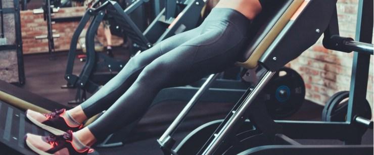 girl using hack squat machine in gym