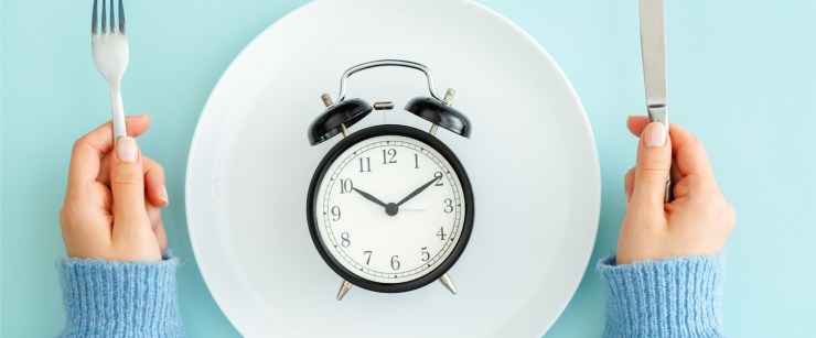 intermittent fasting concept: hands with fork and knife, and clock on a plate
