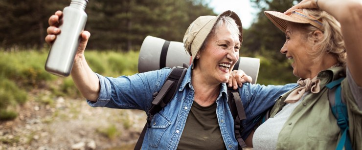 older women embracing in the outdoors while camping