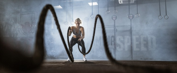 fit woman working out with battle ropes