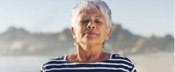 older woman breathing in fresh air outside