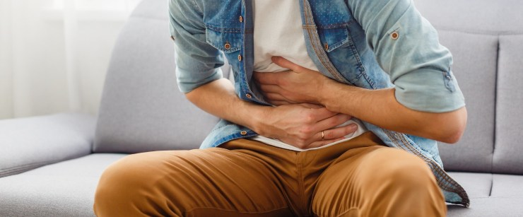 man with stomach ache clutching stomach