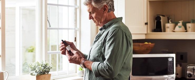 older man holding bottle of CBD oil in his kitchen