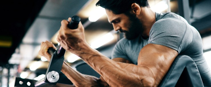 fit man doing biceps curls at the gym