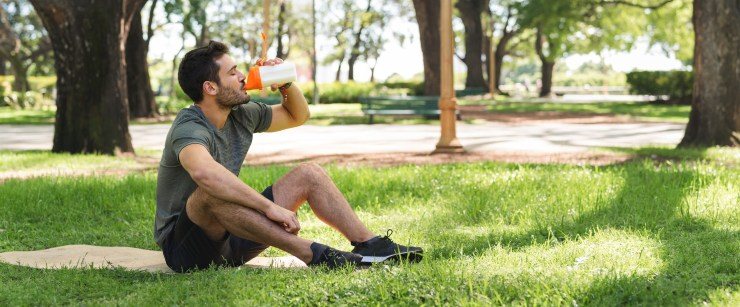 young man drinking a protein shake in the park